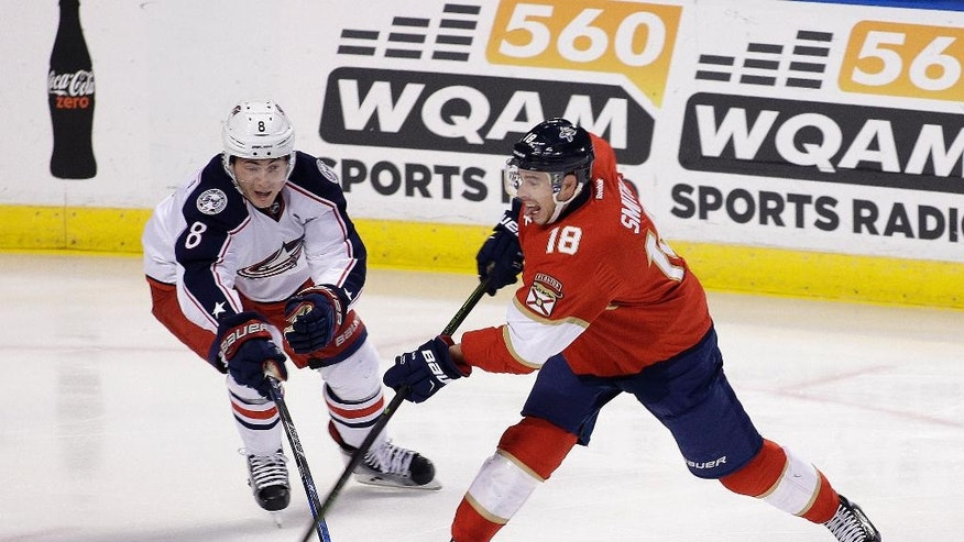 Columbus Blue Jackets defenseman Zach Werenski (8) and Florida Panthers right wing Reilly Smith (18) go for the puck during the first period of an NHL hockey game, Saturday, Nov. 26, 2016, in Sunrise, Fla. (AP Photo/Terry Renna)