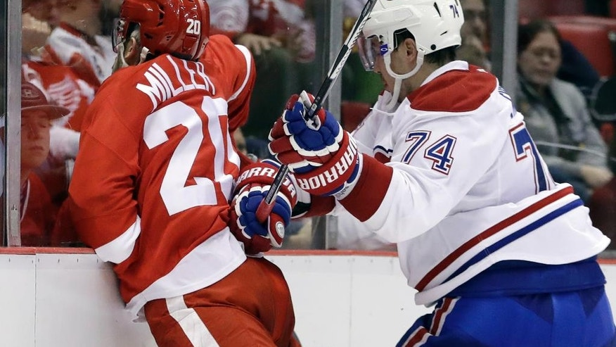 Montreal Canadiens defenseman Alexei Emelin (74) checks Detroit Red Wings left wing Drew Miller (20) into the glass during the second period of an NHL hockey game, Saturday, Nov. 26, 2016, in Detroit. (AP Photo/Carlos Osorio)