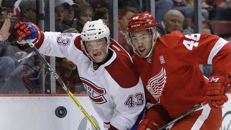 Montreal Canadiens left wing Daniel Carr (43) and Detroit Red Wings defenseman Ryan Sproul (48) chase the puck during the first period of an NHL hockey game, Saturday, Nov. 26, 2016, in Detroit. (AP Photo/Carlos Osorio)
