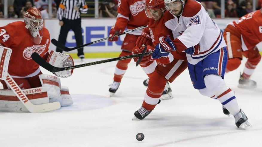 Detroit Red Wings defenseman Brendan Smith (2) and Montreal Canadiens left wing Phillip Danault (24) chase the puck next to Detroit Red Wings goalie Petr Mrazek (34) during the first period of an NHL hockey game, Saturday, Nov. 26, 2016, in Detroit. (AP Photo/Carlos Osorio)