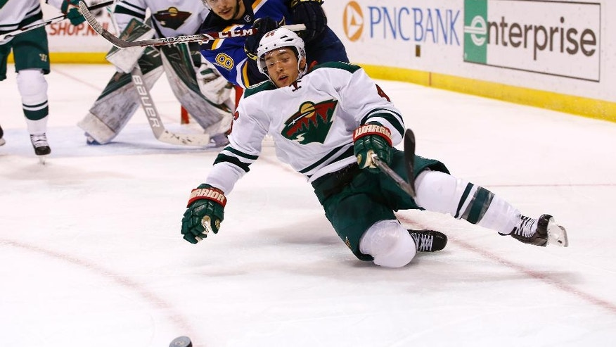 Minnesota Wild's Jared Spurgeon, front, falls to the ice as he and St. Louis Blues' Ty Rattie chase a loose puck during the second period of an NHL hockey game Saturday, Nov. 26, 2016, in St. Louis. (AP Photo/Billy Hurst)