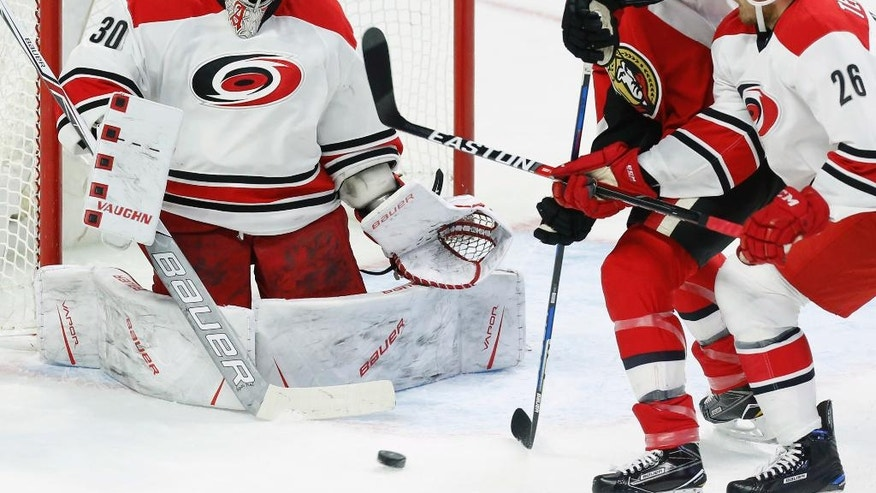 Carolina Hurricanes goaltender Cam Ward (30) makes a save on Ottawa Senators' Chris Neil (25) as Hurricanes' Matt Tennyson (26) defends during the first period of an NHL hockey game in Ottawa, Ontario, Saturday, Nov. 26, 2016. (Fred Chartrand/The Canadian Press via AP)