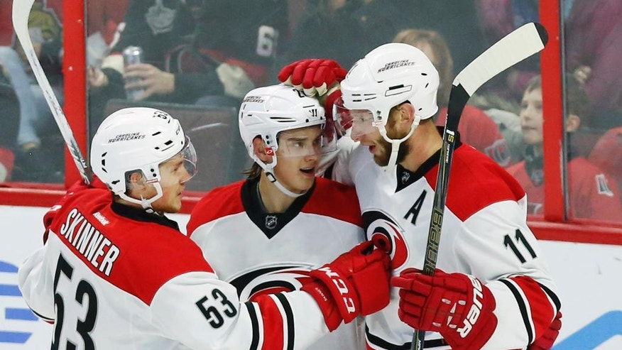 Carolina Hurricanes' Sebastian Aho (20) celebrates his goal against the Ottawa Senators with teammates Jordan Staal (11) and Jeff Skinner (53) during the first period of an NHL hockey game in Ottawa, Ontario, Saturday, Nov. 26, 2016. (Fred Chartrand/The Canadian Press via AP)