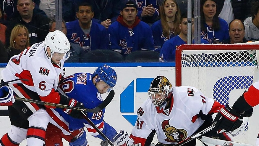 Ottawa Senators goaltender Craig Anderson (41) makes a save on a shot by New York Rangers' Jesper Fast (19) as Senators' Chris Wideman (6) helps out during the first period of an NHL hockey game in New York, Sunday, Nov. 27, 2016. (AP Photo/Rich Schultz)