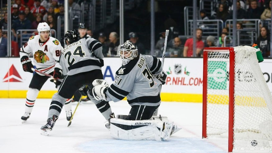 Chicago Blackhawks right wing Patrick Kane, left, scores a goal past Los Angeles Kings defenseman Derek Forbort, center, and goalie Peter Budaj, right, during the first period of an NHL hockey game Saturday, Nov. 26, 2016, in Los Angeles. (AP Photo/Danny Moloshok)