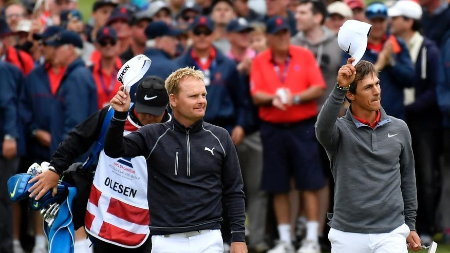 Denmark's Soren Kjeldsen, left, and teammate Thorbjorn Olesen wave to the crowd as they walk the 18th fairway during their match at the World Cup of Golf at Kingston Heath in Melbourne, Australia, Sunday, Nov. 27, 2016. (AP Photo/Andrew Brownbill)