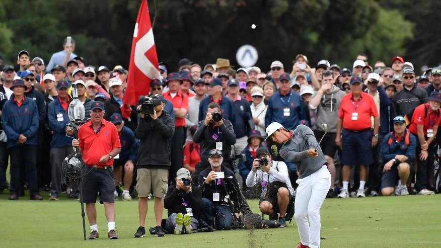 Denmark's Thorbjorn Olesen plays an approach shot into the 18th green during his match at the World Cup of Golf at Kingston Heath in Melbourne, Australia, Sunday, Nov. 27, 2016. (AP Photo/Andrew Brownbill)
