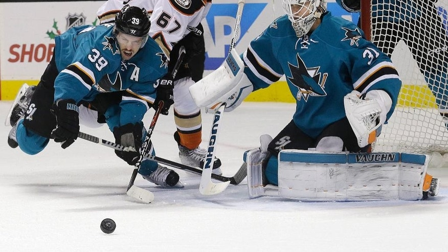 San Jose Sharks center Logan Couture (39) reaches for the puck in front of goalie Martin Jones (31) and Anaheim Ducks center Rickard Rakell (67), from Sweden, during the second period of an NHL hockey game in San Jose, Calif., Saturday, Nov. 26, 2016. (AP Photo/Jeff Chiu)