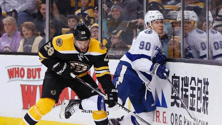 Boston Bruins' Dominic Moore (28) checks Tampa Bay Lightning's Vladislav Namestnikov (90), of Russia, during the first period of an NHL hockey game in Boston, Sunday, Nov. 27, 2016. (AP Photo/Michael Dwyer)