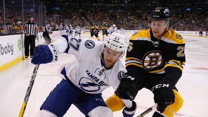 Tampa Bay Lightning's Jonathan Drouin (27) and Boston Bruins' Brandon Carlo (25) battle along the boards during the first period of an NHL hockey game in Boston, Sunday, Nov. 27, 2016. (AP Photo/Michael Dwyer)