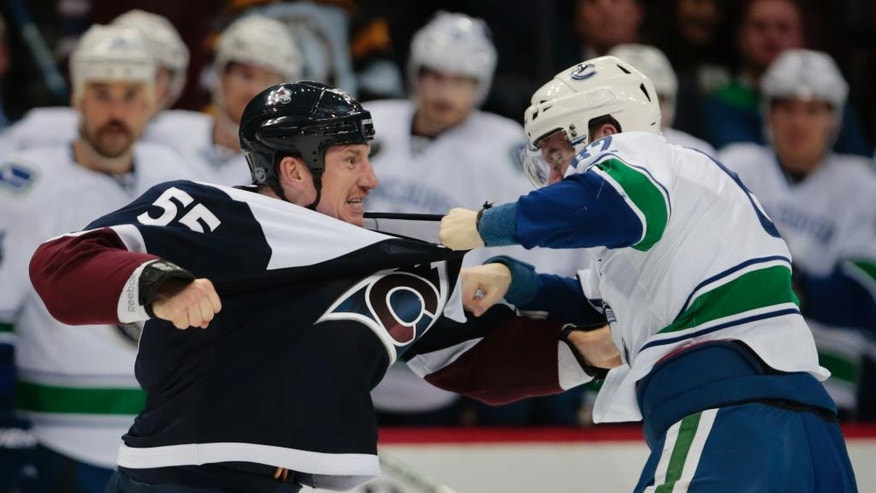 Colorado Avalanche left wing Cody McLeod (55) fights Vancouver Canucks center Joseph Labate (62) during the second period of an NHL hockey game, Saturday, Nov. 26, 2016 in Denver.(AP Photo/Joe Mahoney)