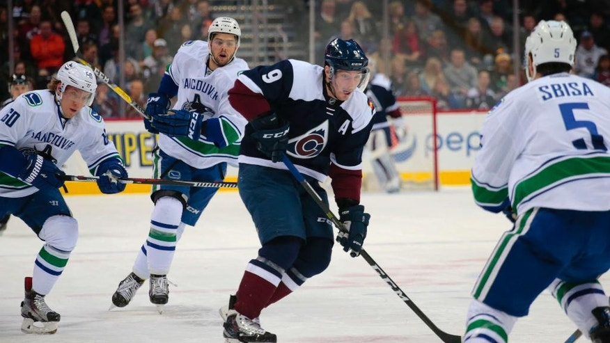 Colorado Avalanche center Matt Duchene (9) carries the puck against Vancouver Canucks defenseman Troy Stecher (51), center Michael Chaput (45) and defenseman Luca Sbisa (5) during the first period of an NHL hockey game, Saturday, Nov. 26, 2016 in Denver.(AP Photo/Joe Mahoney)