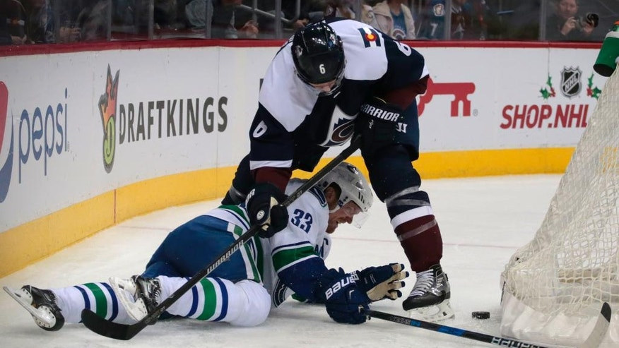 Vancouver Canucks center Henrik Sedin (33) and Colorado Avalanche defenseman Erik Johnson (6) tie up for the puck behind the net in the second period of an NHL hockey game, Saturday, Nov. 26, 2016, in Denver. (AP Photo/Joe Mahoney)