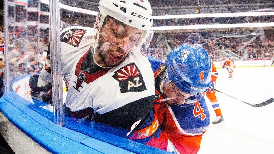 Arizona Coyotes' Tobias Rieder (8) and Edmonton Oilers' Kris Russell (4) battle in the corner during first period NHL hockey action in Edmonton, Alberta on Sunday Nov. 27, 2016. (Jason Franson/The Canadian Press via AP)