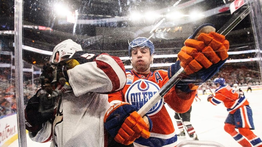 Arizona Coyotes' Connor Murphy (5) is checked by Edmonton Oilers' Milan Lucic (27) during second period NHL hockey action in Edmonton, Alberta on Sunday Nov. 27, 2016. (Jason Franson/The Canadian Press via AP)
