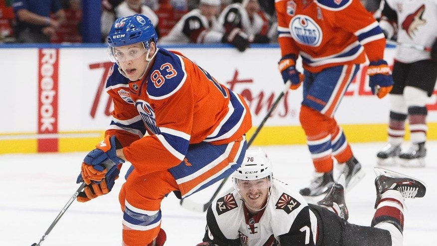 Arizona Coyotes' Laurent Dauphin (76) tries to get the puck from Edmonton Oilers' Matthew Benning (83) during first period NHL hockey action in Edmonton, Alberta on Sunday Nov. 27, 2016. (Jason Franson/The Canadian Press via AP)