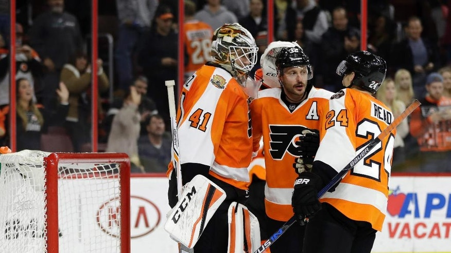 Philadelphia Flyers' Anthony Stolarz, from left, Mark Streit and Matt Read celebrate after an NHL hockey game against the Calgary Flames, Sunday, Nov. 27, 2016, in Philadelphia. Philadelphia won 5-3. (AP Photo/Matt Slocum)