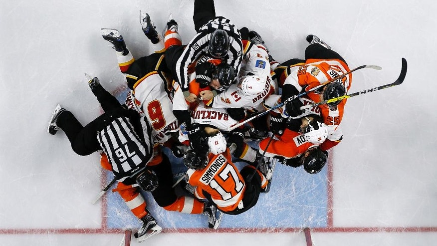 Referees try to break up a fight between the Philadelphia Flyers and the Calgary Flames during the third period of an NHL hockey game, Sunday, Nov. 27, 2016, in Philadelphia. (AP Photo/Matt Slocum)