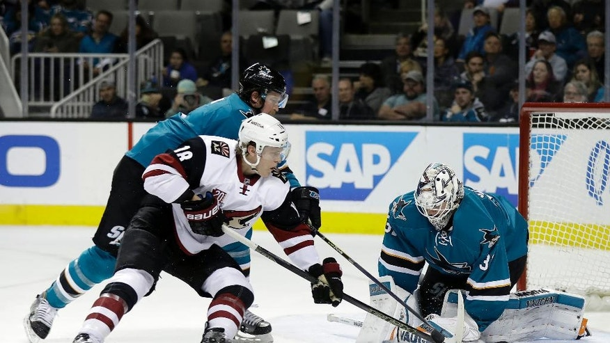 San Jose Sharks goalie Martin Jones, right, stops a shot in front of Arizona Coyotes' Christian Dvorak (18) and Sharks defenseman Paul Martin during the second period of an NHL hockey game, Tuesday, Nov. 29, 2016, in San Jose, Calif. (AP Photo/Marcio Jose Sanchez)