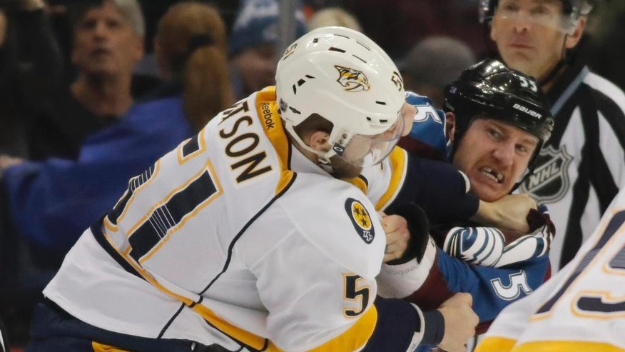 Nashville Predators left wing Austin Watson, front, fights with Colorado Avalanche left wing Cody McLeod in the second period of an NHL hockey game, Tuesday, Nov. 29, 2016, in Denver. (AP Photo/David Zalubowski)
