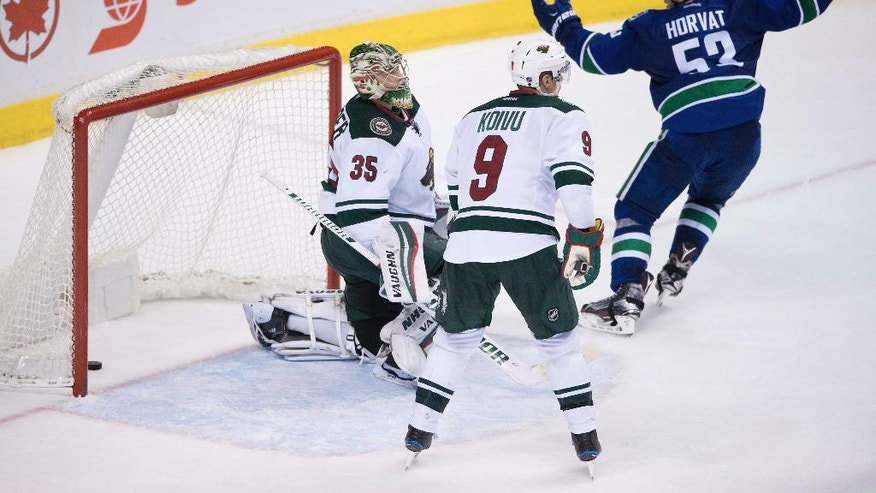 Vancouver Canucks' Bo Horvat, right, celebrates a goal by Sven Baertschi as Minnesota Wild goalie Darcy Kuemper, left, and Wild's Mikko Koivu, of Finland, watch during the third period of an NHL hockey game Tuesday, Nov. 29, 2016, in Vancouver, British Columbia. (Darryl Dyck/The Canadian Press via AP)