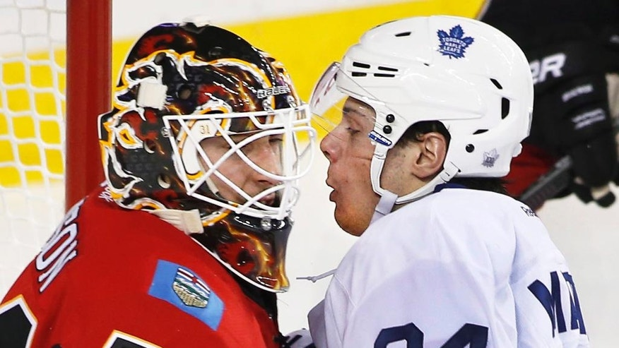 Toronto Maple Leafs' Auston Matthews, right, comes face-to-mask in the crease with Calgary Flames goalie Chad Johnson during the second period of an NHL hockey game Wednesday, Nov. 30, 2016, in Calgary, Alberta. (Larry MacDougal/The Canadian Press via AP)