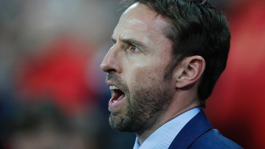 FILE - In this Tuesday, Nov. 15, 2016 file photo, England's interim manager Gareth Southgate sings the national anthem prior to the international friendly soccer match between England and Spain at the Wembley stadium, London. The English Football Association has hired Gareth Southgate on a four-year contract to remain in charge of the national team on Wednesday, Nov. 30, 2016. (AP Photo/Kirsty Wigglesworth, file)