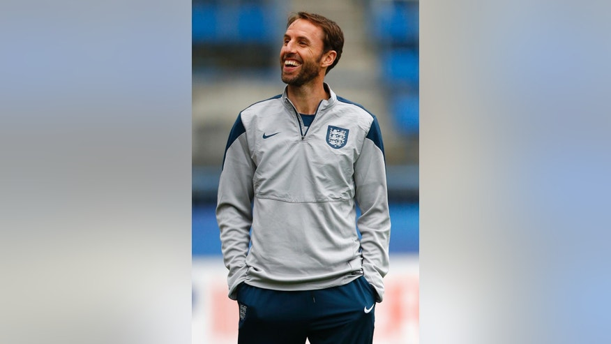 FILE - In this Tuesday, June 23, 2015 file photo, England's coach Gareth Southgate laughs during a session at the Euro U21 soccer championship in Olomouc, Czech Republic. The English Football Association has hired Gareth Southgate on a four-year contract to remain in charge of the national team on Wednesday, Nov. 30, 2016. (AP Photo/Matthias Schrader, file)
