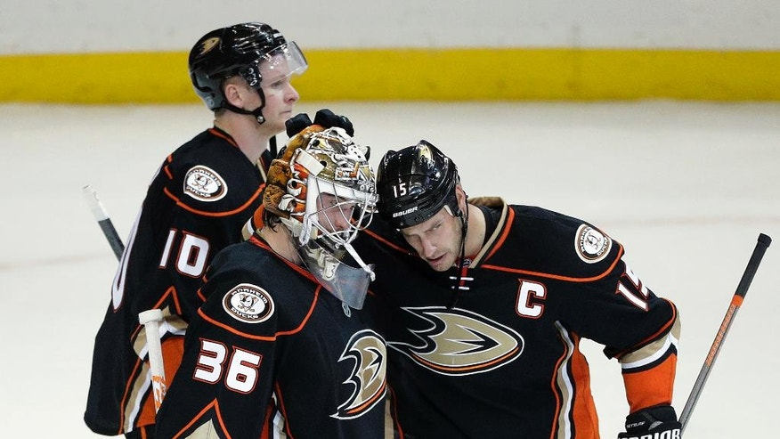 Anaheim Ducks goalie John Gibson, front left, and teammate Ryan Getzlaf celebrate the team's 2-1 win against the Montreal Canadiens in an NHL hockey game Tuesday, Nov. 29, 2016, in Anaheim, Calif. Skating behind them is Corey Perry. (AP Photo/Jae C. Hong)