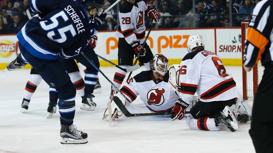 Winnipeg Jets' Mark Scheifele (55) scores on New Jersey Devils goaltender Cory Schneider (35) as Damon Severson (28) and Andy Greene (6) defend during the second period of an NHL hockey game Tuesday, Nov. 29, 2016, in Winnipeg, Manitoba. (John Woods/The Canadian Press via AP)