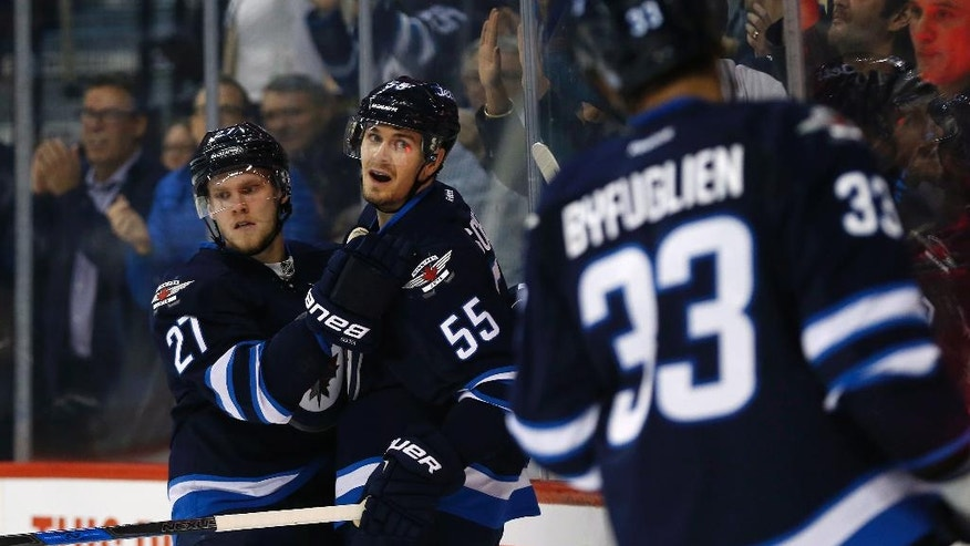 Winnipeg Jets' Mark Scheifele (55), Nikolaj Ehlers (27) and Dustin Byfuglien (33) celebrate Scheifele's goal against the New Jersey Devils during the second period of an NHL hockey game Tuesday, Nov. 29, 2016, in Winnipeg, Manitoba. (John Woods/The Canadian Press via AP)