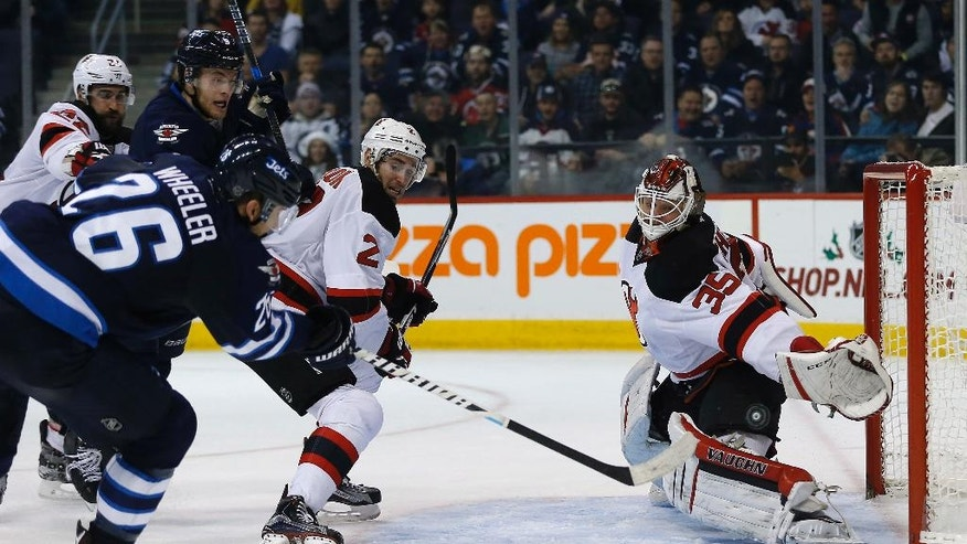 Winnipeg Jets' Blake Wheeler (26) scores on New Jersey Devils goaltender Cory Schneider (35) as John Moore (2) defends during the second period of an NHL hockey game Tuesday, Nov. 29, 2016, in Winnipeg, Manitoba. (John Woods/The Canadian Press via AP)