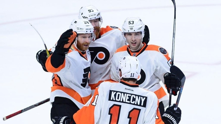 Philadelphia Flyers' Claude Giroux (28), left, celebrates his game winning overtime goal against the Ottawa Senators with teammates Jakub Voracek (93), Shayne Gostisbehere (53) and Travis Konecny (11) in an NHL hockey game, Thursday, Dec. 1, 2016 in Ottawa, Ontario.  (Sean Kilpatrick/The Canadian Press via AP)