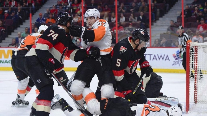 Philadelphia Flyers' Shayne Gostisbehere, middle, and Michael Raffl, right, mix it up with Ottawa Senators' Mark Borowiecki, left, and Cody Ceci during the first period of an NHL hockey game, Thursday, Dec. 1, 2016 in Ottawa, Ontario.  (Sean Kilpatrick/The Canadian Press via AP)