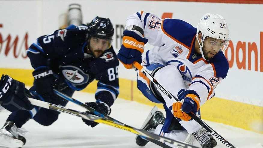 Winnipeg Jets' Mathieu Perreault (85) goes down as Edmonton Oilers' Darnell Nurse (25) clears the puck during the second period of an NHL game in Winnipeg, Manitoba, Thursday, Dec. 1, 2016. (John Woods/The Canadian Press via AP)