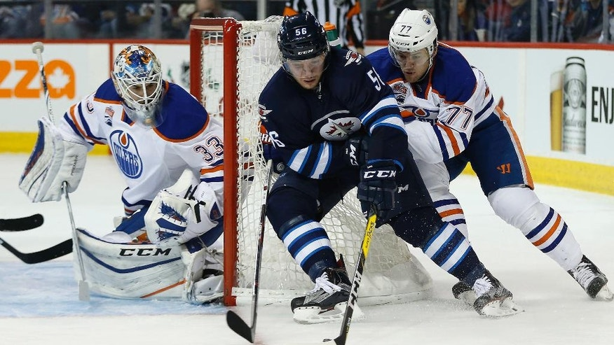 Winnipeg Jets' Marko Dano (56) attempts the wrap-around as Edmonton Oilers goaltender Cam Talbot (33) covers his net and Oscar Klefbom (77) defends during the second period of an NHL game in Winnipeg, Manitoba, Thursday, Dec. 1, 2016. (John Woods/The Canadian Press via AP)