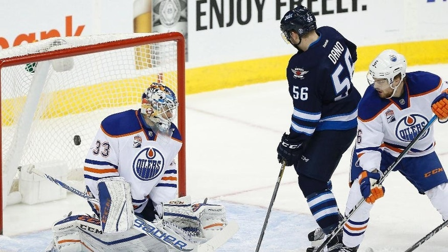 Winnipeg Jets' Marko Dano (56) and Edmonton Oilers' Adam Larsson (6) look on as Jets' Patrik Laine's (29) shot gets past Oilers goaltender Cam Talbot (33) during the first period of an NHL game in Winnipeg, Manitoba, Thursday, Dec. 1, 2016. (John Woods/The Canadian Press via AP)