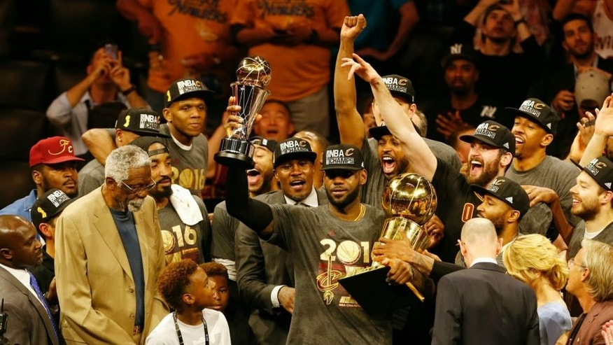 TOPSHOT - Cleveland Cavaliers forward LeBron James hoists the Larry O'Brien and the Finals MVP trophies after defeating the Golden State Warriors to win the NBA Finals on June 19, 2016 in Oakland, California. Powered by an amazing effort from LeBron James, the Cleveland Cavaliers completed the greatest comeback in NBA Finals history, dethroning defending champion Golden State 93-89 to capture their first NBA title. The Cavaliers won the best-of-seven series 4-3 to claim the first league crown in their 46-season history and deliver the first major sports champion to Cleveland since the 1964 NFL Browns, ending the longest such title drought for any American city. / AFP / Beck Diefenbach (Photo credit should read BECK DIEFENBACH/AFP/Getty Images)