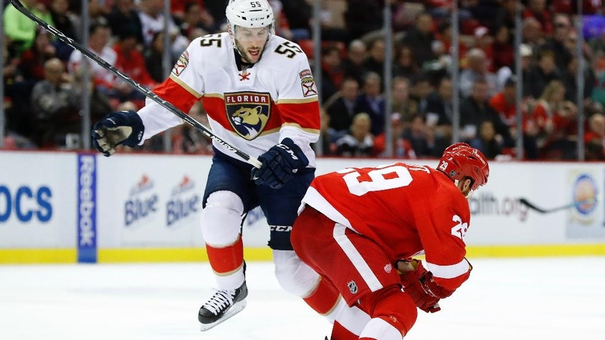 Florida Panthers defenseman Jason Demers (55) evades a check by Detroit Red Wings center Steve Ott during the first period of an NHL hockey game Thursday, Dec. 1, 2016, in Detroit. (AP Photo/Paul Sancya)
