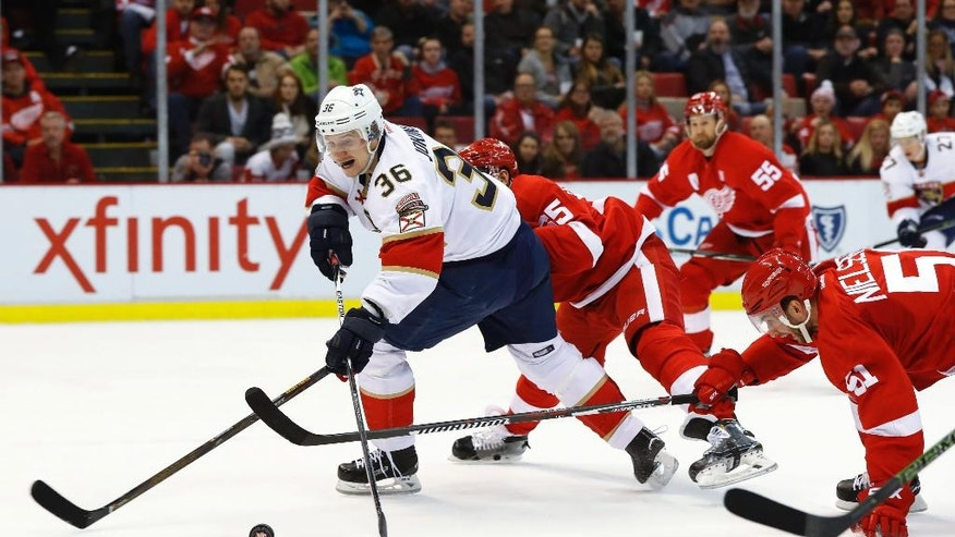 Florida Panthers left wing Jussi Jokinen (36) shoots as Detroit Red Wings' Danny DeKeyser (65) and Frans Nielsen (51) defend during the first period of an NHL hockey game Thursday, Dec. 1, 2016, in Detroit. (AP Photo/Paul Sancya)