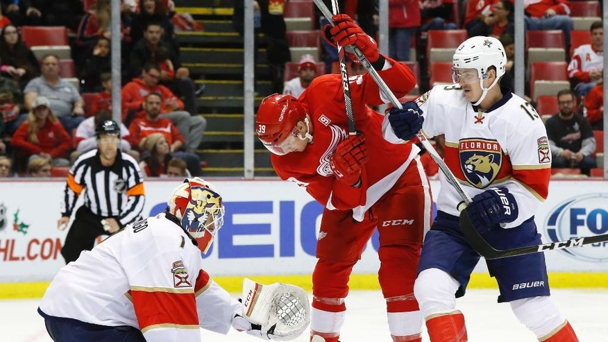 Florida Panthers goalie Roberto Luongo (1) deflects a shot as Detroit Red Wings right wing Anthony Mantha (39) looks for the puck as Mark Pysyk (13) defends during the second period of an NHL hockey game Thursday, Dec. 1, 2016, in Detroit. (AP Photo/Paul Sancya)