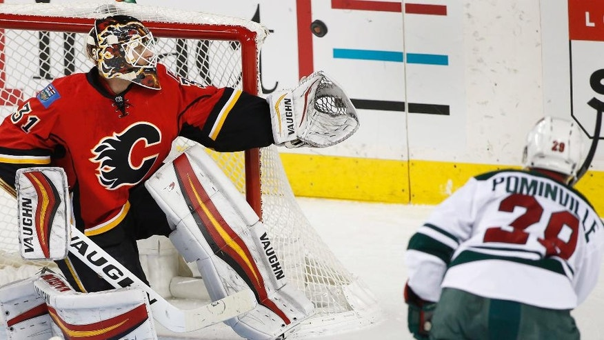 Calgary Flames' goalie Chad Johnson, left, makes a save against Minnesota Wild's Jason Pominville during first-period NHL hockey game action in Calgary, Alberta, Friday, Dec. 2, 2016. (Larry MacDougal/The Canadian Press via AP)