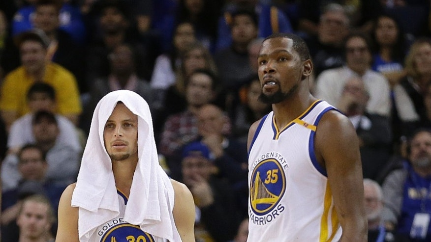 The Golden State Warriors' Stephen Curry, left, and Kevin Durant watch during the second half of Thursday's game.