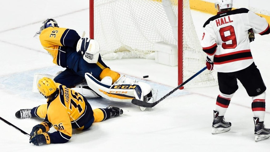 New Jersey Devils left wing Taylor Hall (9) watches a shot by teammate Michael Cammalleri get past Nashville Predators goalie Pekka Rinne (35), of Finland, for a goal in overtime of an NHL hockey game Saturday, Dec. 3, 2016, in Nashville, Tenn. The Devils won 5-4. (AP Photo/Mark Zaleski)