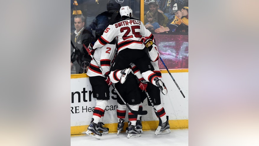 New Jersey Devils left wing Michael Cammalleri, center, is mobbed by teammates after scoring a goal against the Nashville Predators in overtime of an NHL hockey game, Saturday, Dec. 3, 2016, in Nashville, Tenn. The Devils won 5-4. (AP Photo/Mark Zaleski)
