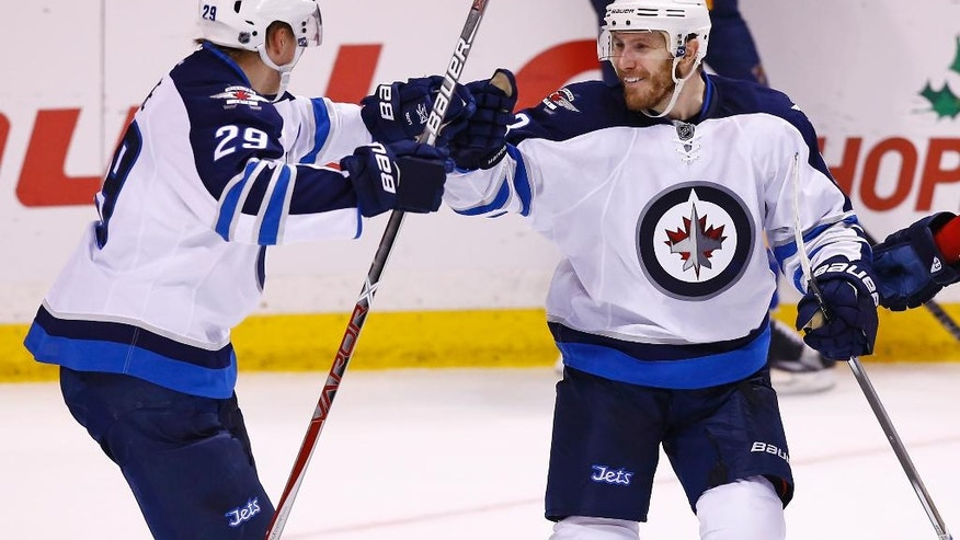 Winnipeg Jets' Bryan Little, right, celebrates with Patrik Laine, of Finland, after scoring the game-winning goal in overtime of an NHL hockey game against the St. Louis Blues, Saturday, Dec. 3, 2016, in St. Louis. The Jets won the game 3-2. (AP Photo/Billy Hurst)