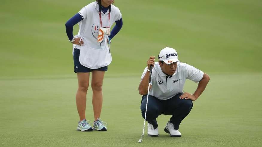 Hideki Matsuyama, right, of Japan, lines up a putt with his caddie Mei Inul, left, on the third hole during the final round at the Hero World Challenge golf tournament, Sunday, Dec. 4, 2016, in Nassau, Bahamas. (AP Photo/Lynne Sladky)