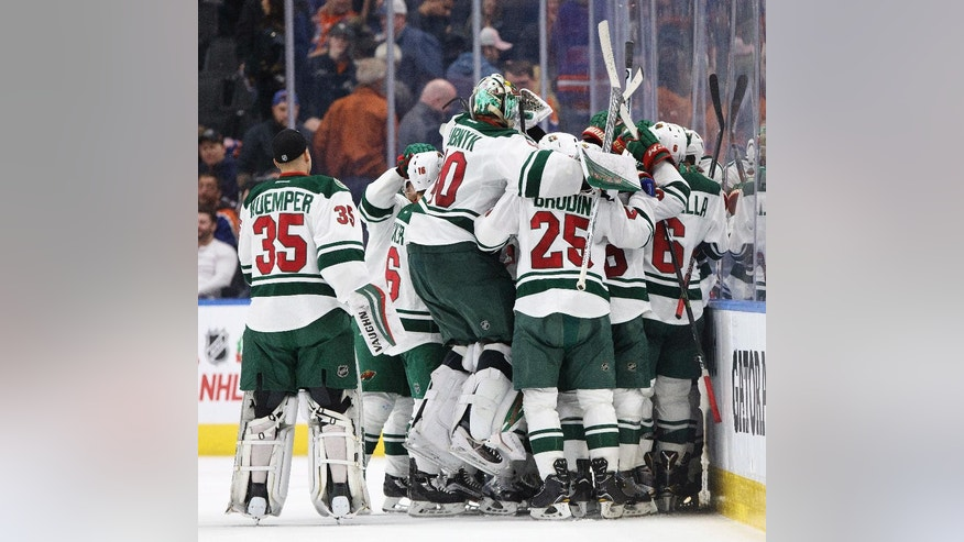 Minnesota Wild celebrate the overtime win over the Edmonton Oilers in an NHL hockey game in Edmonton, Alberta, Sunday, Dec. 4, 2016. (Jason Franson/The Canadian Press via AP)