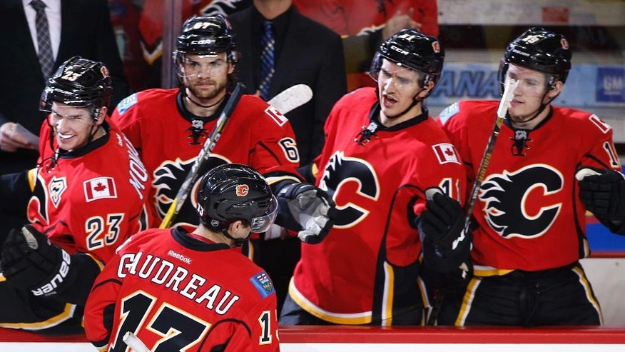 Calgary Flames' Johnny Gaudreau, bottom left, celebrates his goal against the Anaheim Ducks at the bench during the first period of an NHL game in Calgary, Alberta, Sunday, Dec. 4, 2016. (Larry MacDougal/The Canadian Press via AP)