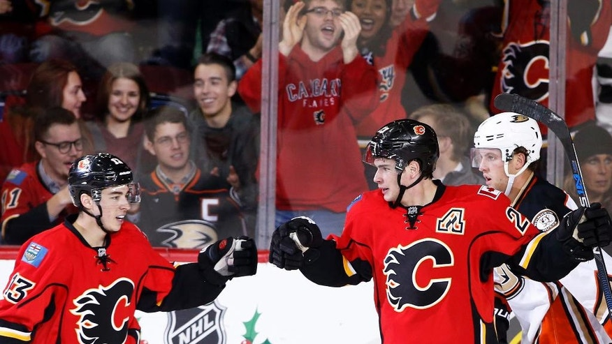 Calgary Flames' Sean Monahan, right, celebrates with Johnny Gaudreau after a goal against the Anaheim Ducks during the second period of an NHL game in Calgary, Alberta, Sunday, Dec. 4, 2016. (Larry MacDougal/The Canadian Press via AP)